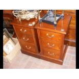 A pair of walnut three drawer bedside chests