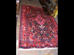 A Middle Eastern rug with red ground - 220cm x 145
