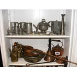 Two shelves of metal ware including pewter and cop