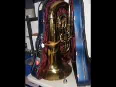 A tuba in case together with mouthpiece