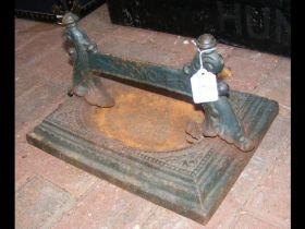 A cast metal foot scraper