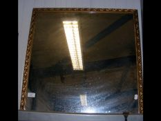 A square wall mirror with leaf detail to frame