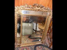 An antique gilt framed cushion mirror 110cm x 85cm