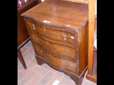 A serpentine fronted chest of three drawers