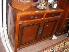 A sideboard with panelled doors and two drawers to