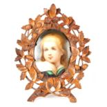 A LATE 19TH CENTURY GERMAN PORCELAIN PLAQUE IN CARVED BLACK FOREST FRAME the leaf work and floral