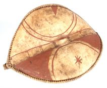 AN AFRICAN HIDE CHIEFTAIN'S SHIELD with bound stitched border and dark red painted decoration 74cm
