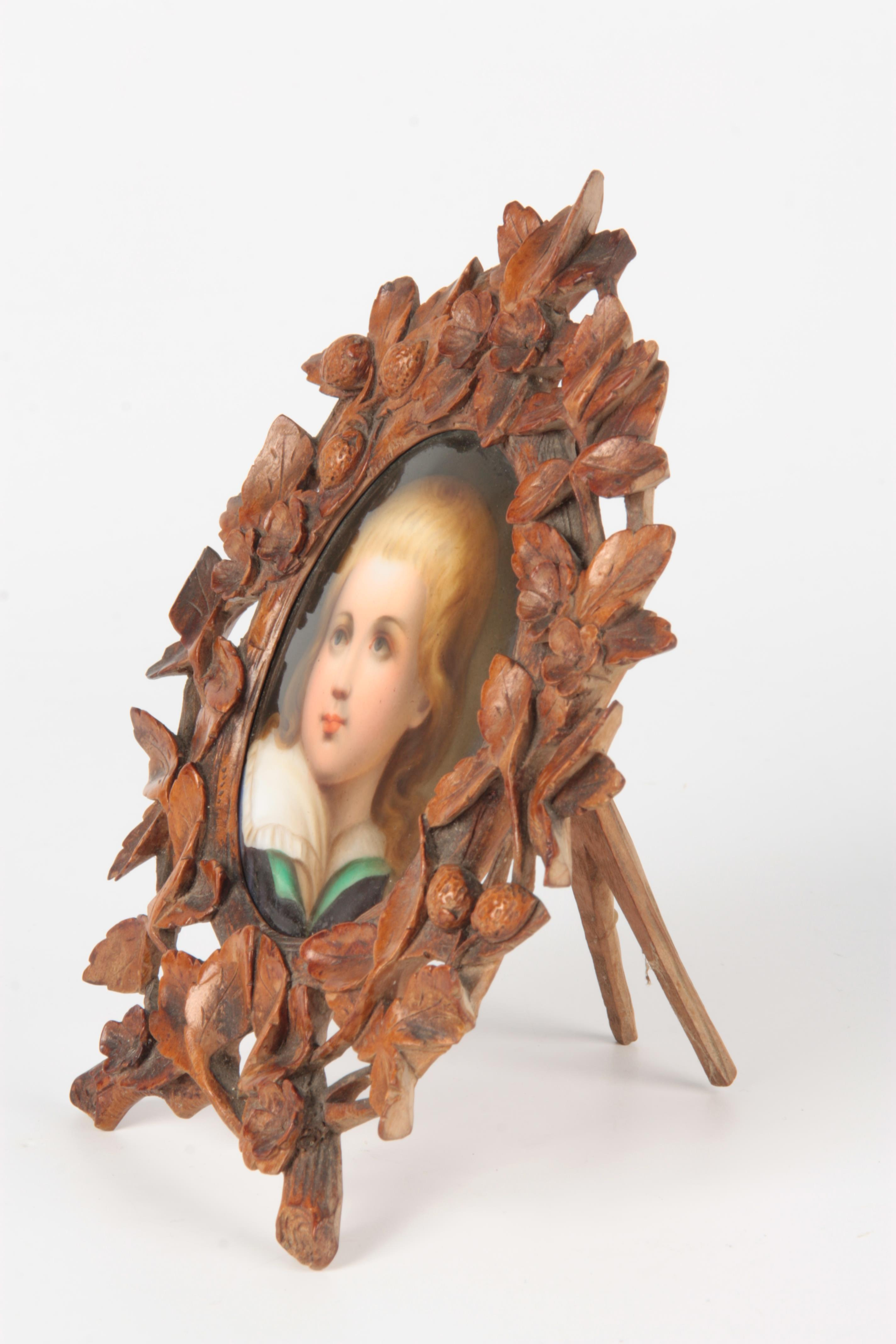 A LATE 19TH CENTURY GERMAN PORCELAIN PLAQUE IN CARVED BLACK FOREST FRAME the leaf work and floral - Image 3 of 5