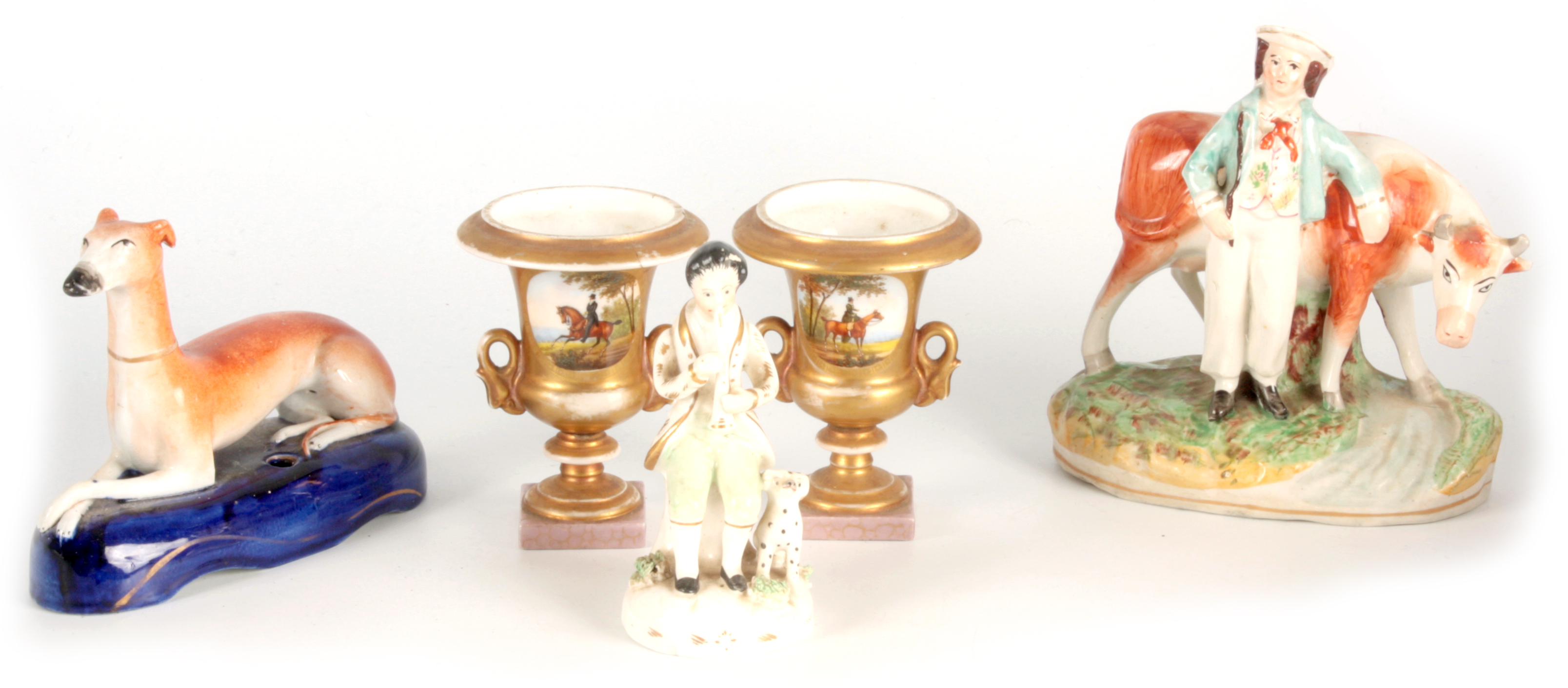 A 19TH CENTURY STAFFORDSHIRE FIGURE depicting a seated piper with dog at foot 12.5cm high A