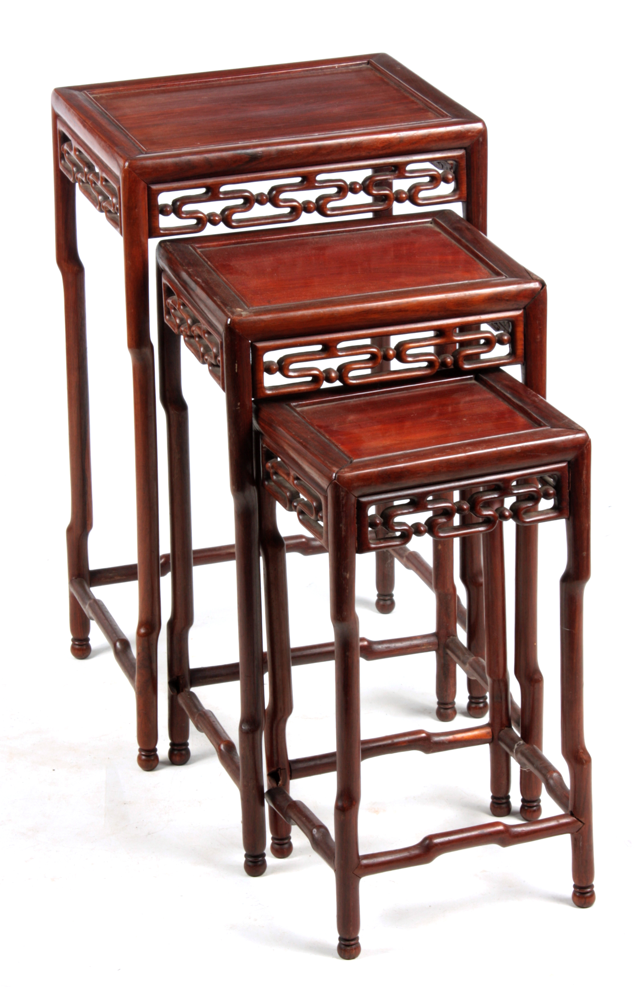 A 20TH CENTURY NEST OF THREE CHINESE HARDWOOD OCCASIONAL TABLES having shaped legs joined by pierced