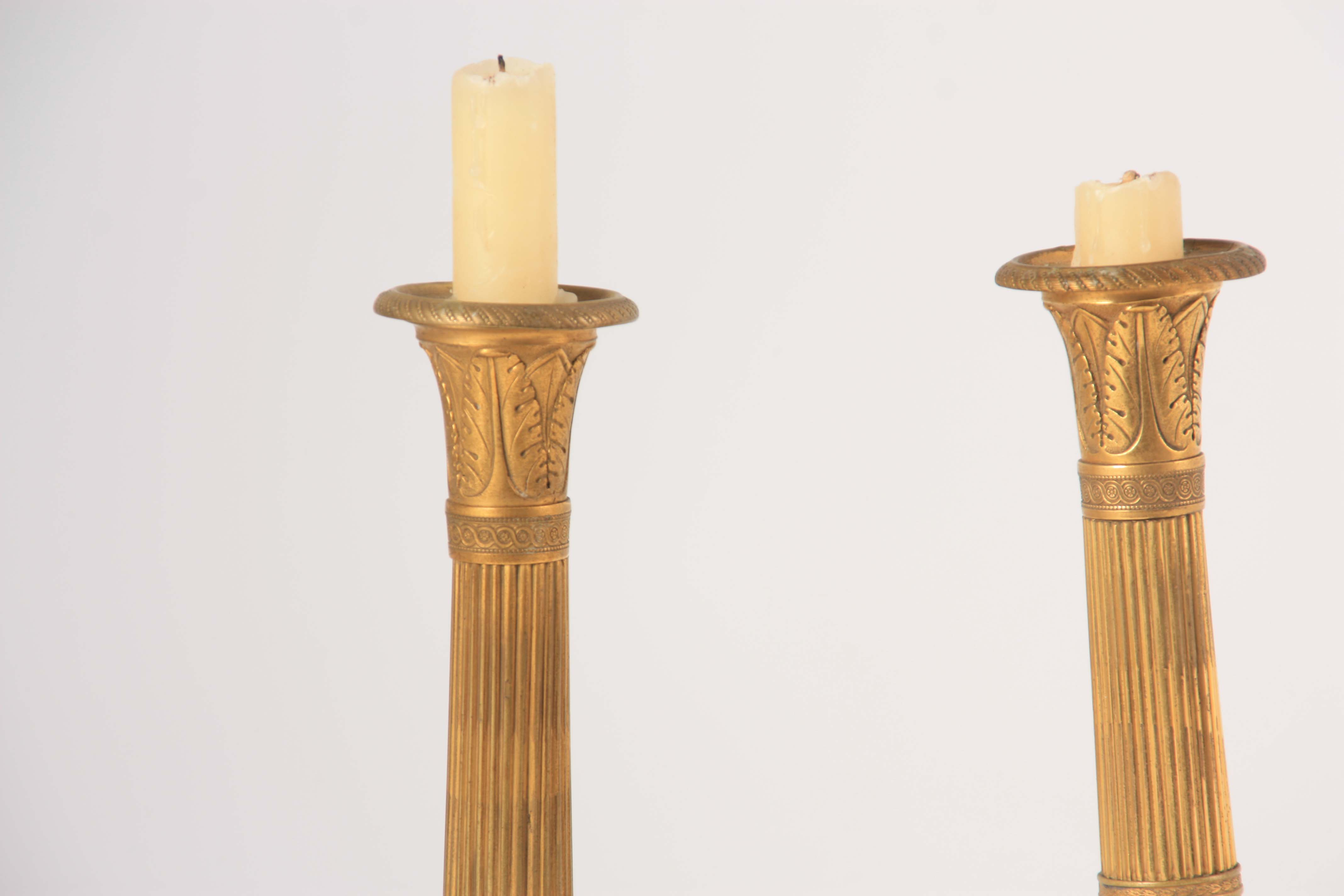 A PAIR OF 19TH CENTURY FRENCH EMPIRE GILT BRASS CANDLESTICKS of classical form with leaf cast scones - Image 2 of 4