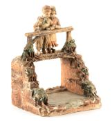 A 19TH CENTURY TERRACOTTA FIGURE GROUP depicting two children on a bridge - the back impressed LMC