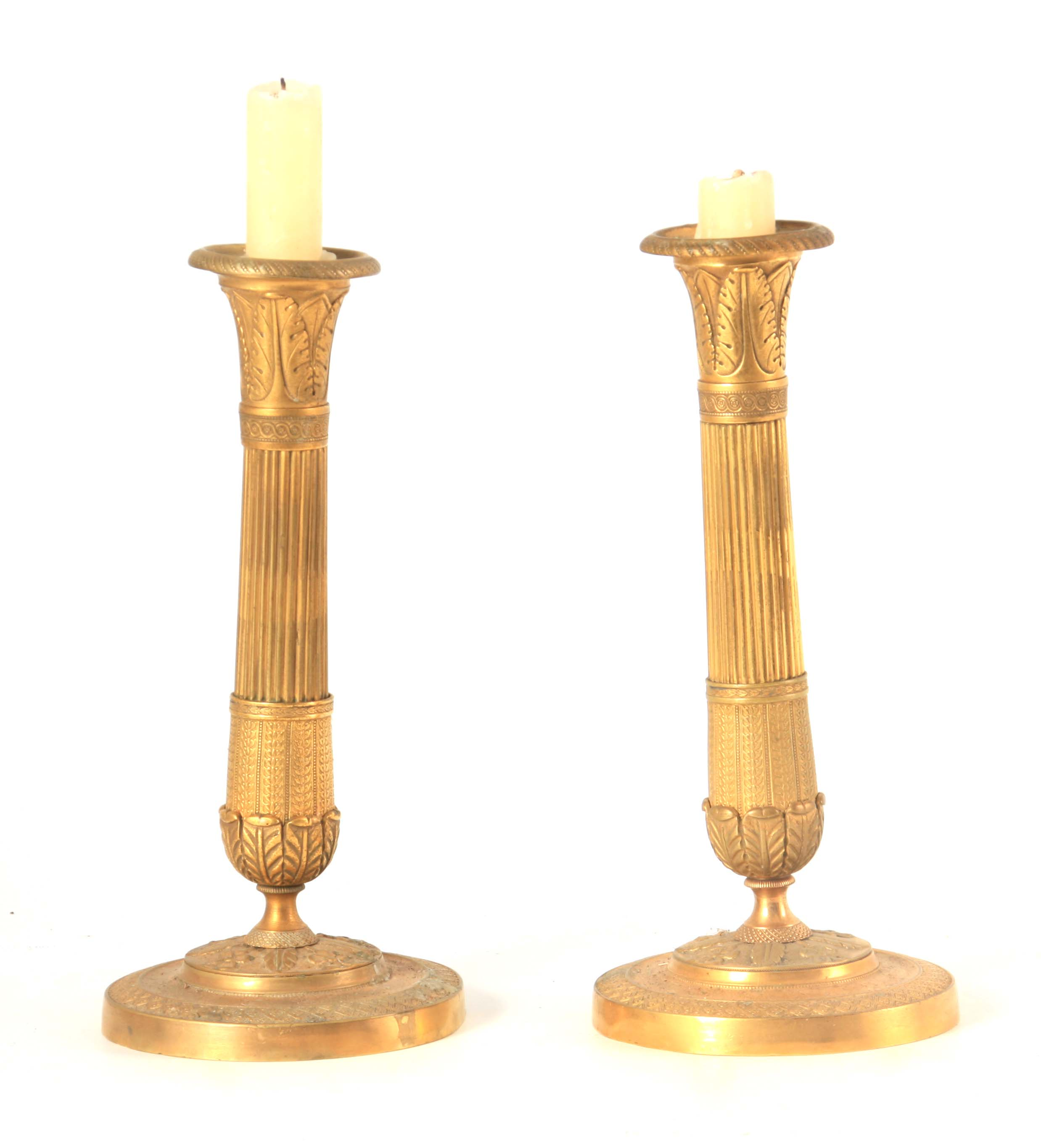 A PAIR OF 19TH CENTURY FRENCH EMPIRE GILT BRASS CANDLESTICKS of classical form with leaf cast scones