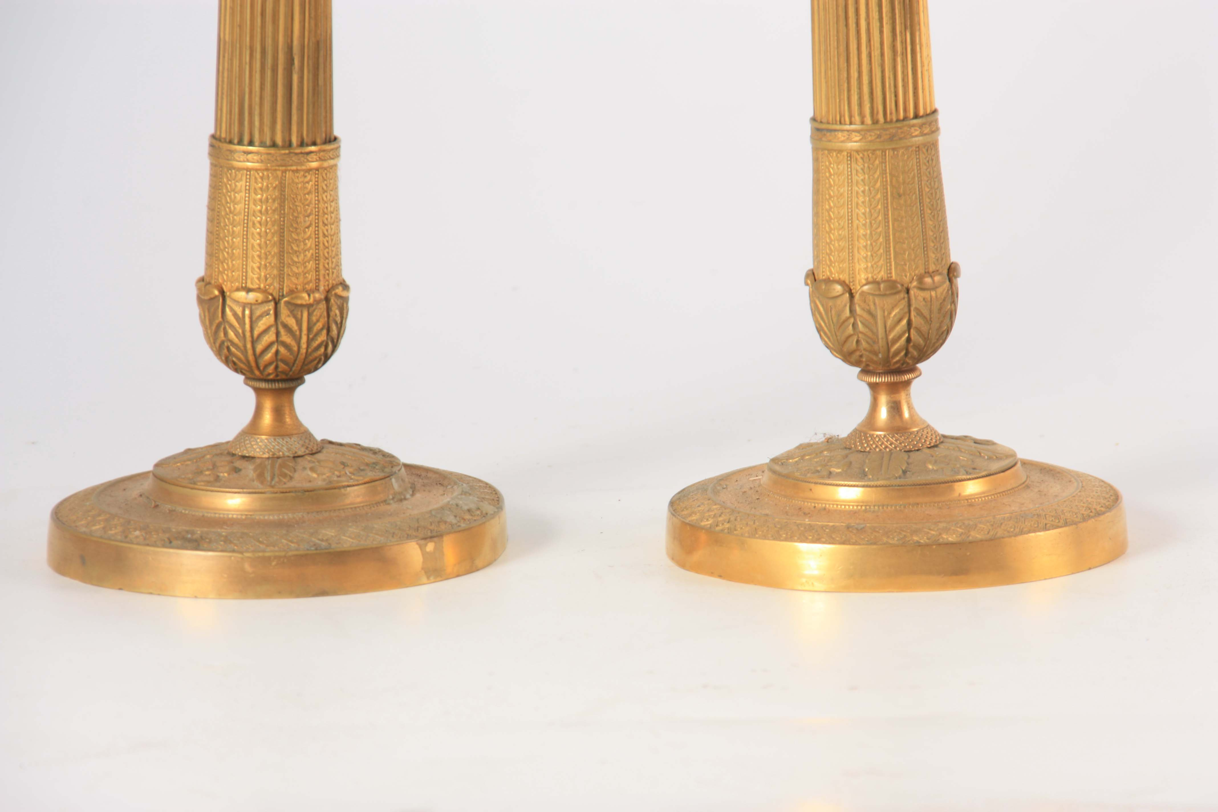 A PAIR OF 19TH CENTURY FRENCH EMPIRE GILT BRASS CANDLESTICKS of classical form with leaf cast scones - Image 3 of 4