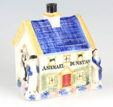 A 19TH CENTURY PRATTWARE POTTERY MONEY BOX with pearlised glaze formed as a house with male and