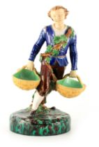 A 19TH CENTURY MINTON MAJOLICA FIGURE finely modelled as a young man carrying baskets coloured in