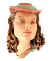 AN ART DECO STYLE POTTERY WALL MASK of a stylised young lady wearing a hat 33cm high