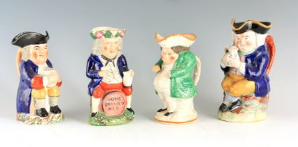 A GROUP OF THREE COLOURFUL SEATED STAFFORDSHIRE TOBY JUGS each clutching a jug of ale 24cm high