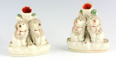 A PAIR OF STAFFORDSHIRE SPILL VASES each modelled as seated poodles dressed in encrusted head and
