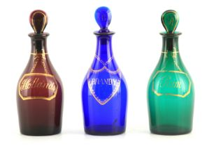 A MATCHED SET OF THREE LATE GEORGIAN COLOURED SPIRIT DECANTERS with gilt work labels for Rum,