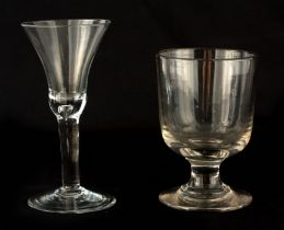 A GEORGIAN PLAIN CLEAR WINE GLASS with flared bowl and teardrop tapering stem on a slightly domed