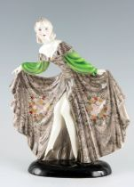 A STYLISH GOLDSCHEIDER STANDING FIGURE OF A YOUNG LADY in an elaborate swept dress 32cm high 27cm