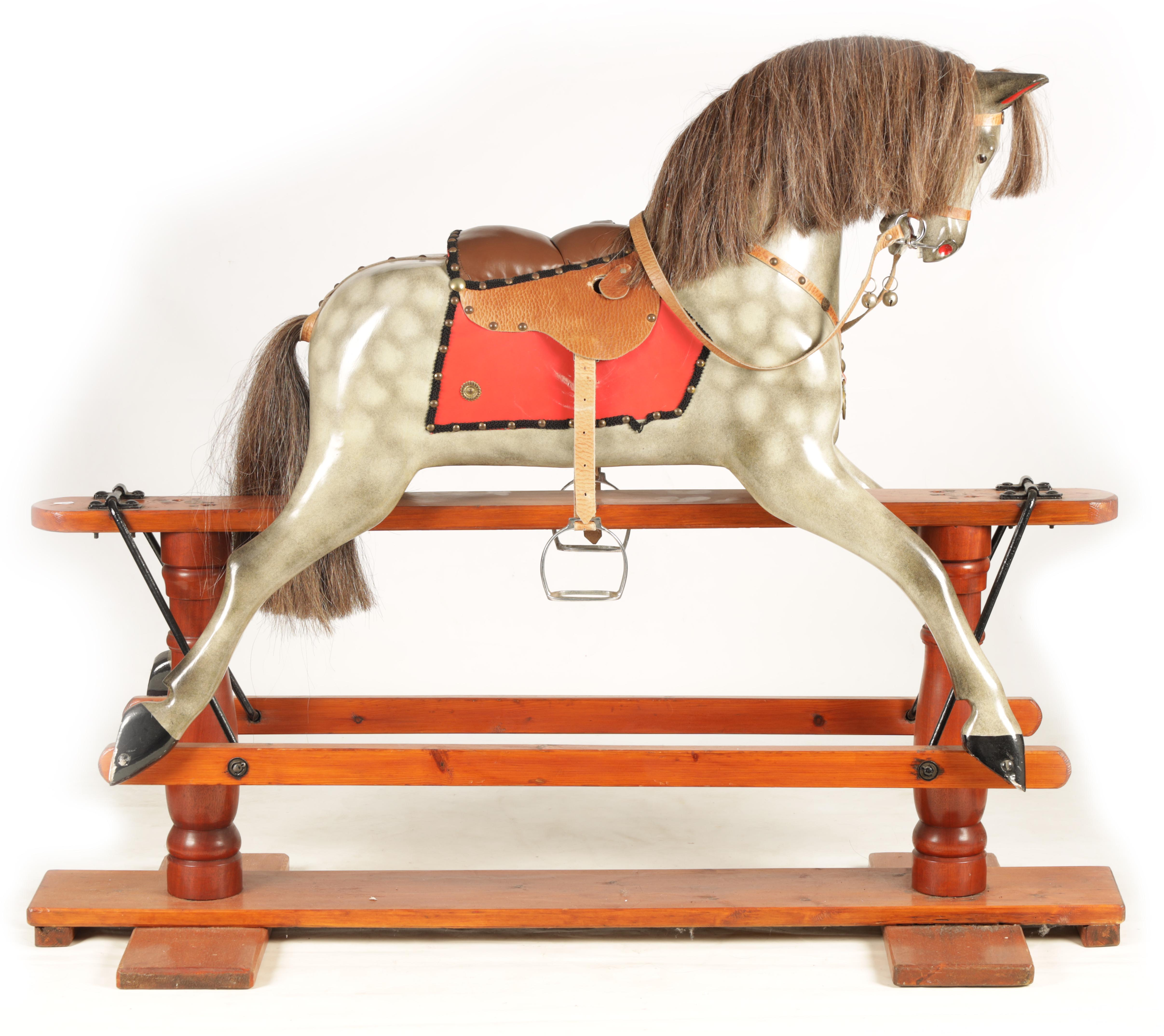 A 20TH CENTURY DAPPLE GREY PAINTED WOODEN ROCKING HORSE with leather seat and bridle 138cm wide