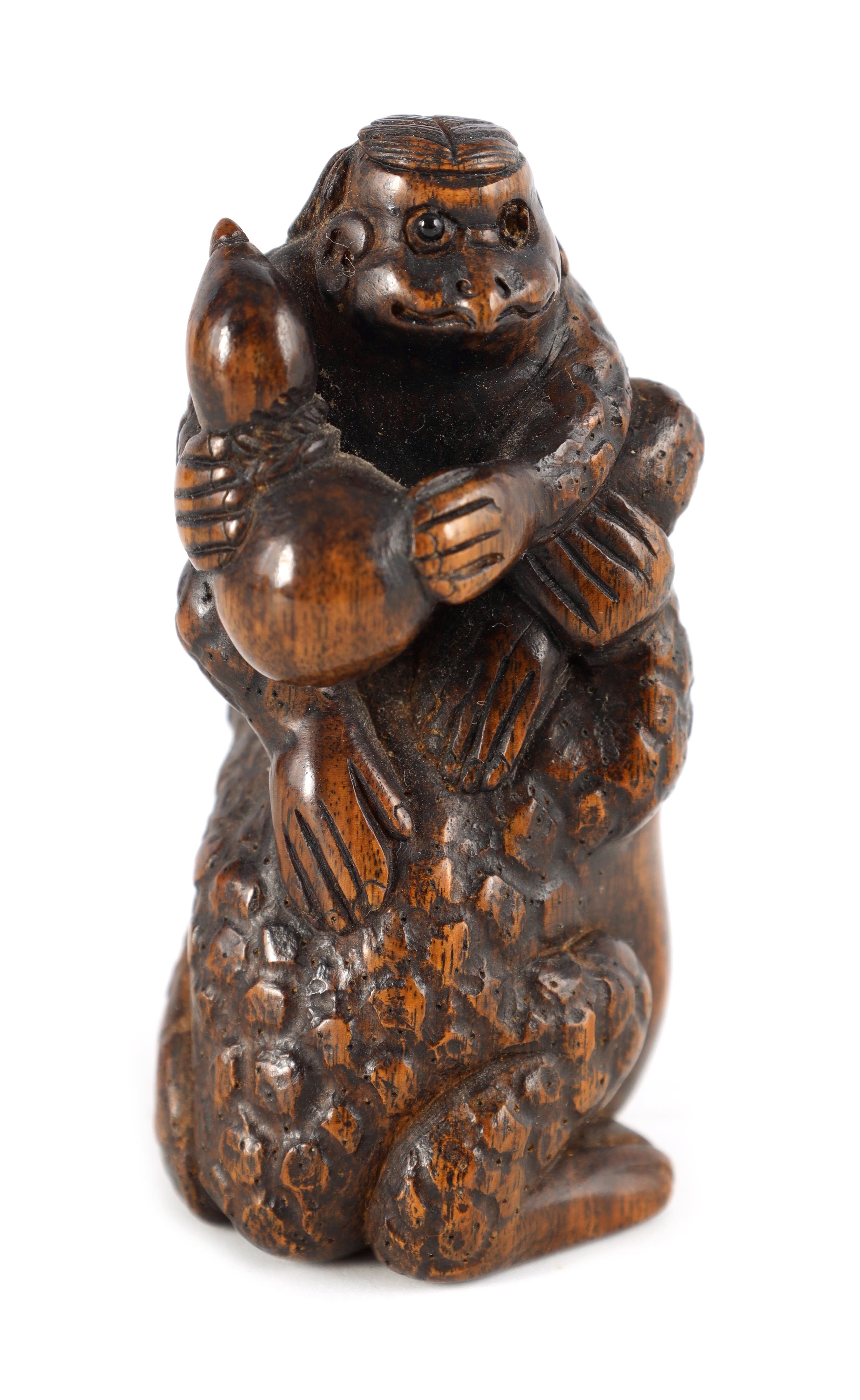 A FINELY CARVED MEIJI PERIOD NETSUKI depicting a monkey holding fruit sat on a toad - h inlaid ivory
