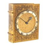 A MID 20TH CENTURY NOVELTY GILT BRASS MANTEL CLOCK modelled as a book with scroll engraved