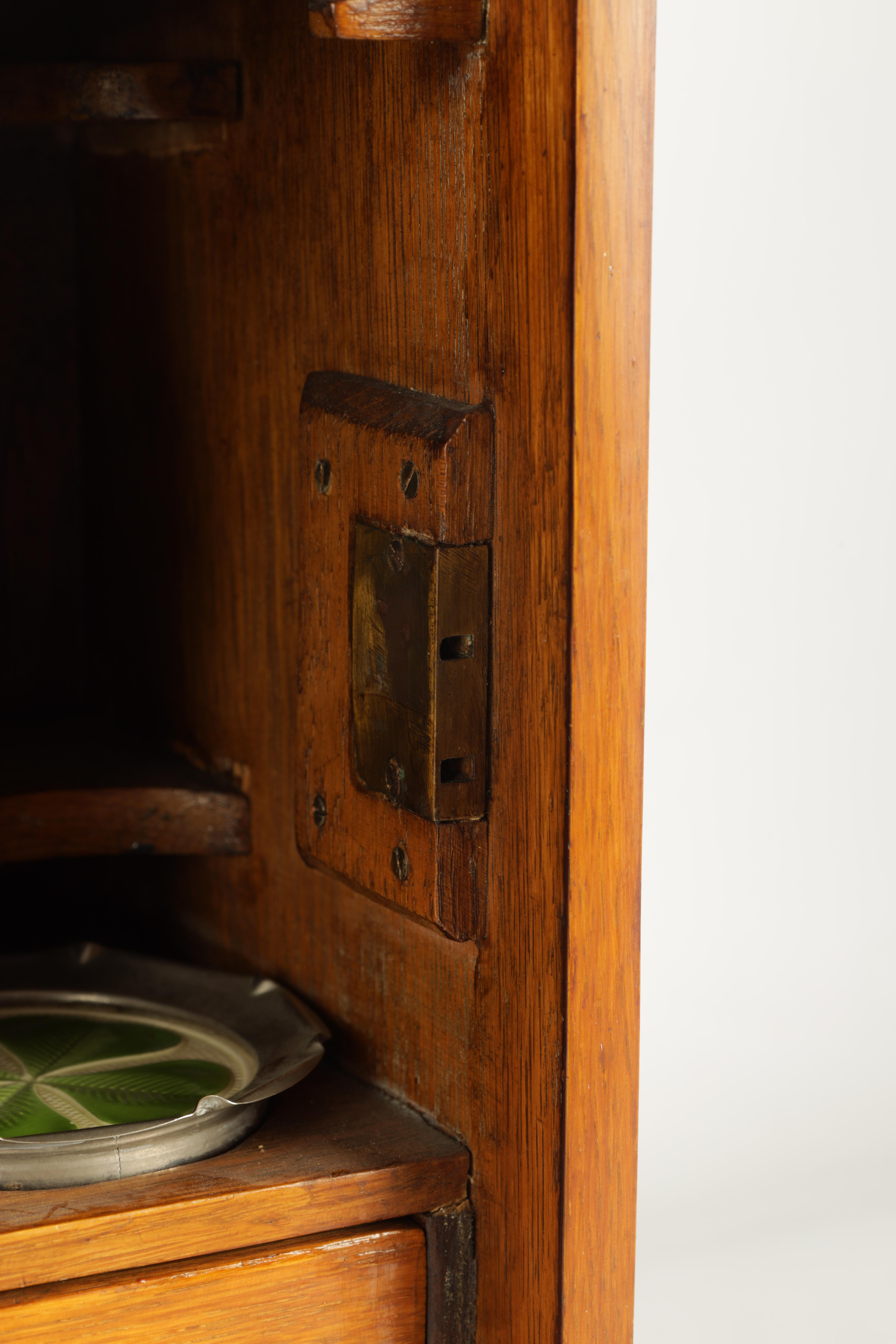 A STYLISH EDWARDIAN OAK SMOKERS CABINET with glazed door enclosing a shelved three drawer interior - Image 8 of 11