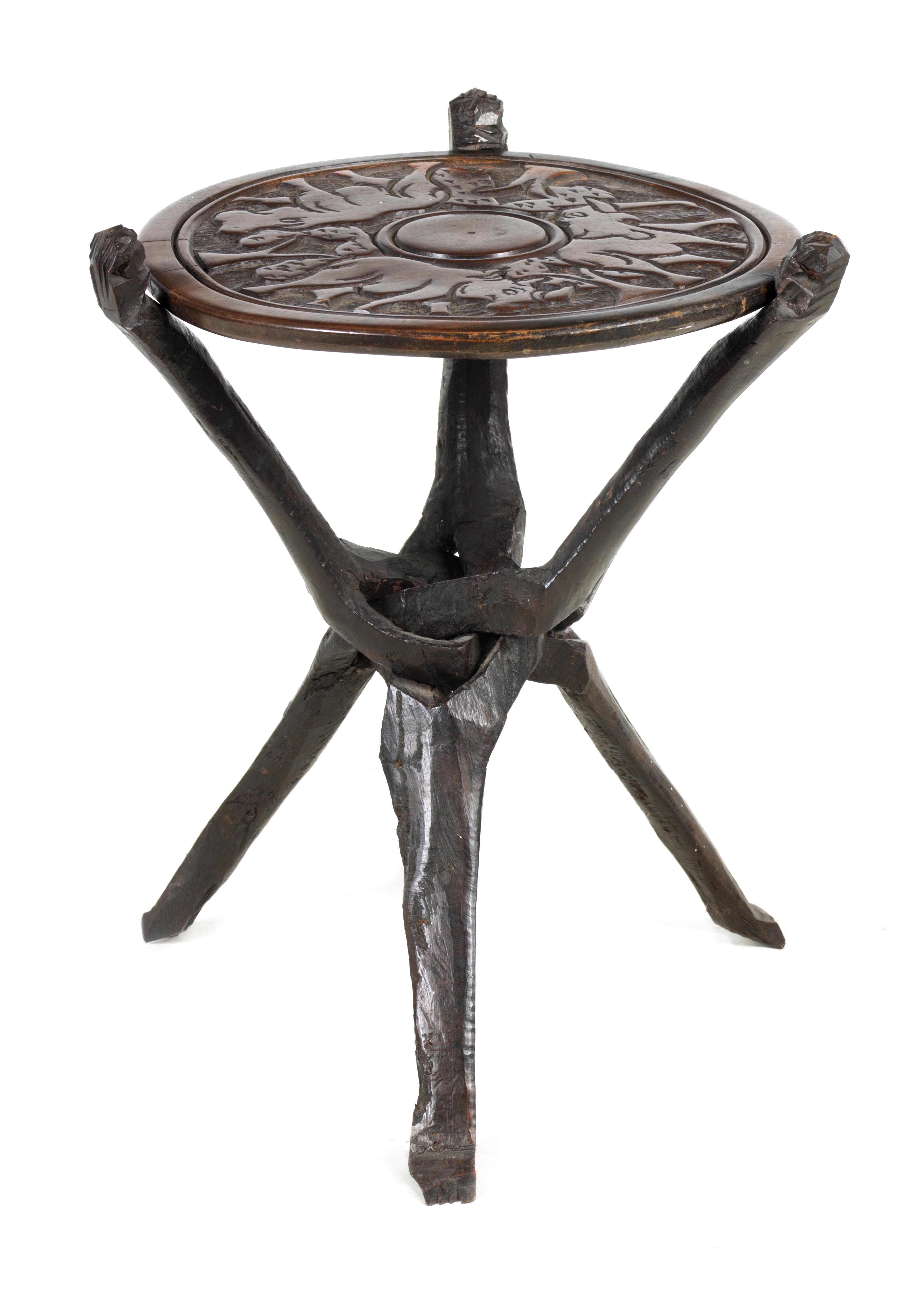 A LATE 19TH CENTURY AFRICAN HARDWOOD FOLDING TABLE the circular top relief carved with Rhinosorus