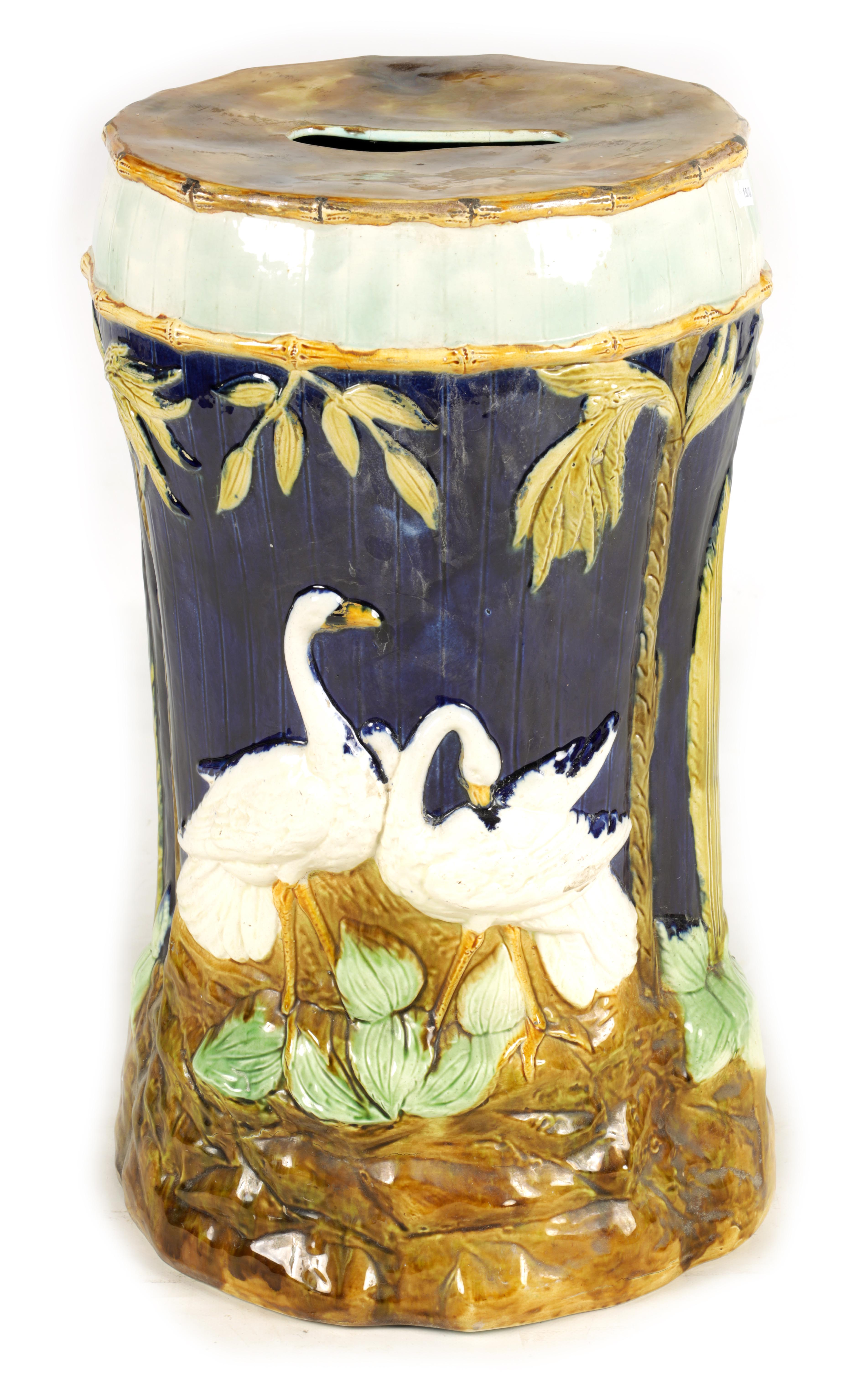 A LATE 19TH CENTURY MAJOLICA GARDEN SEAT decorated with storks between palm trees 54cm high