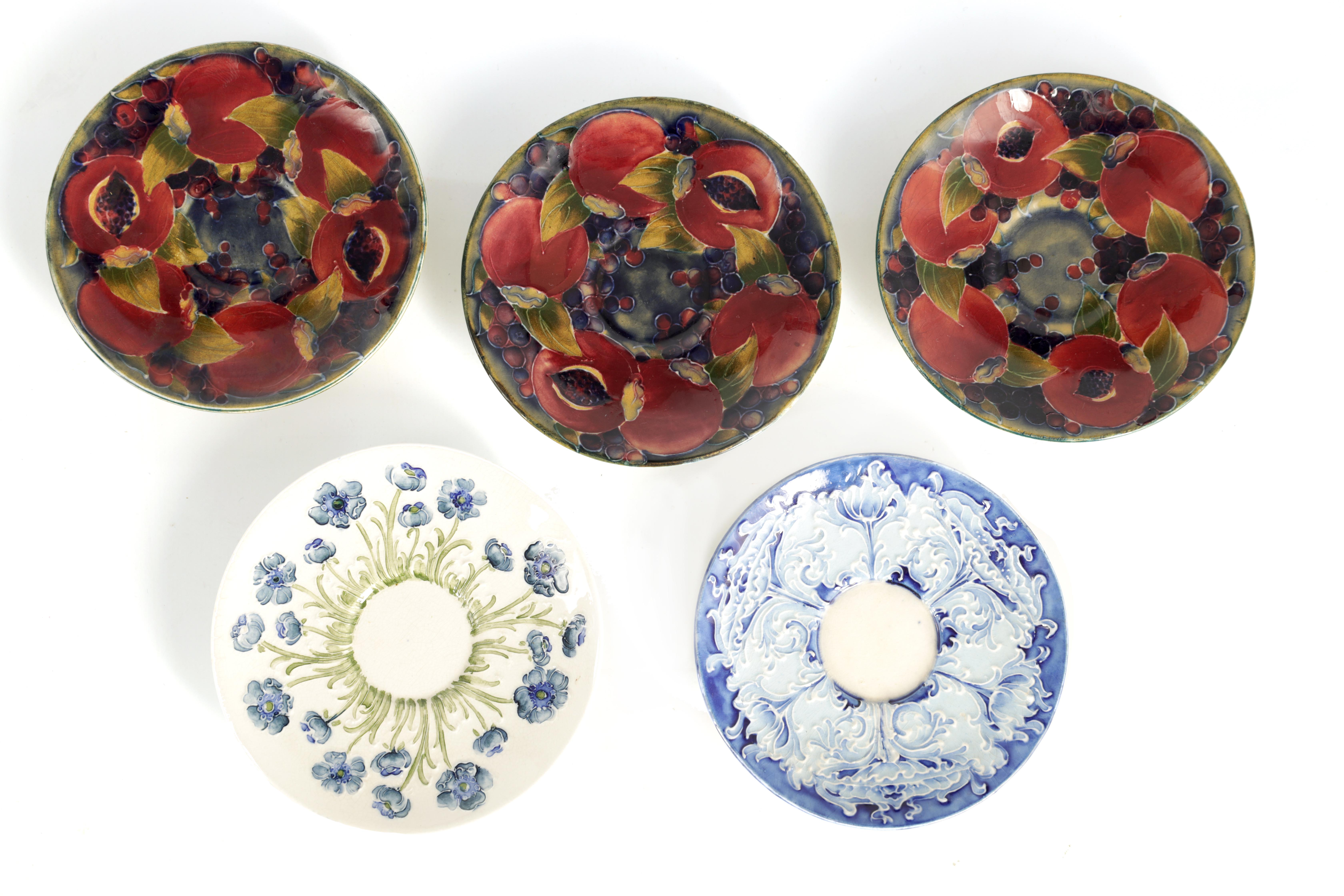A COLLECTION OF FIVE MOORCROFT SAUCERS including three early monogrammed Pomegranate examples, a