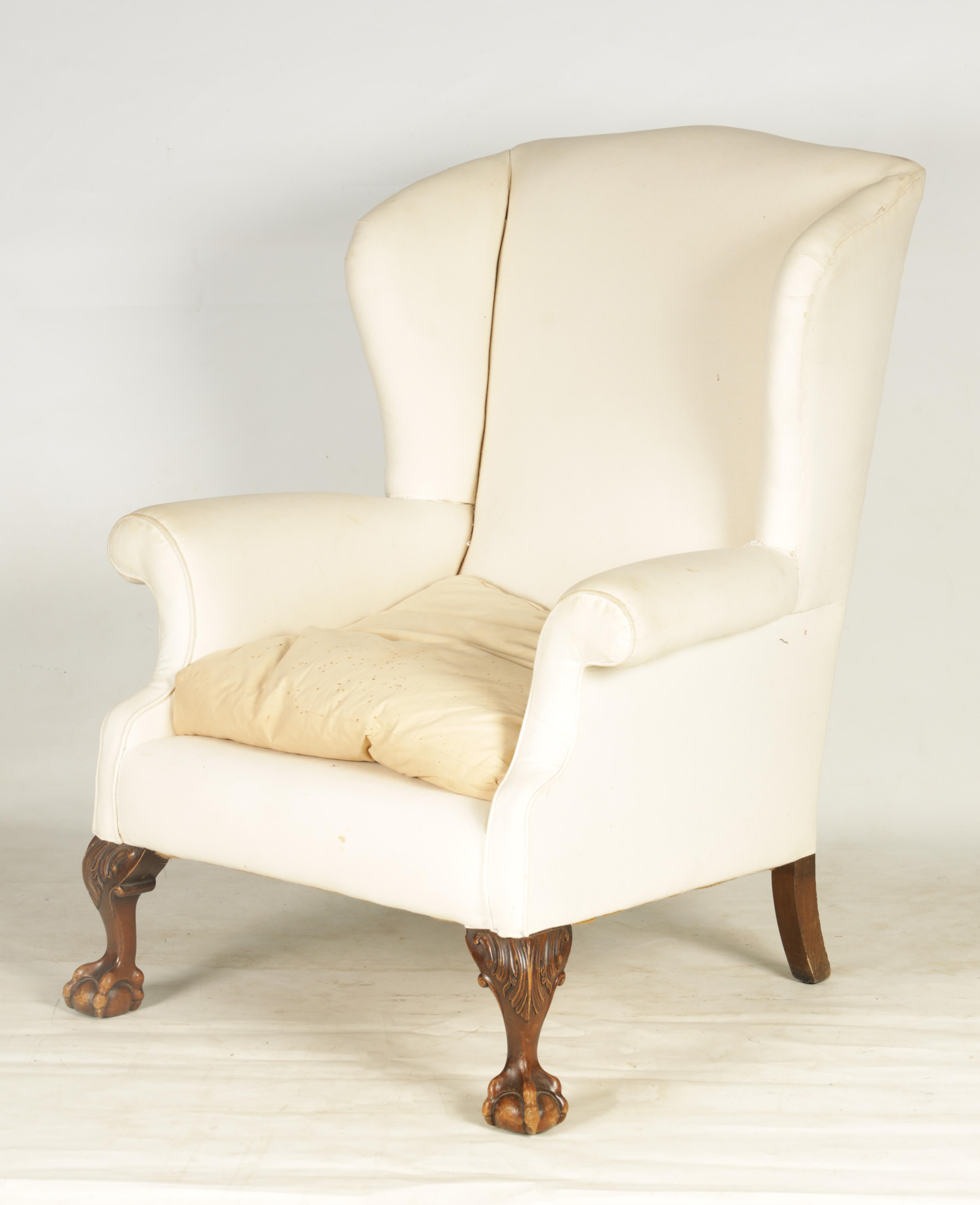 A LATE 19TH CENTURY GEORGE I STYLE WINGBACK UPHOLSTERED ARMCHAIR with mahogany leaf carved