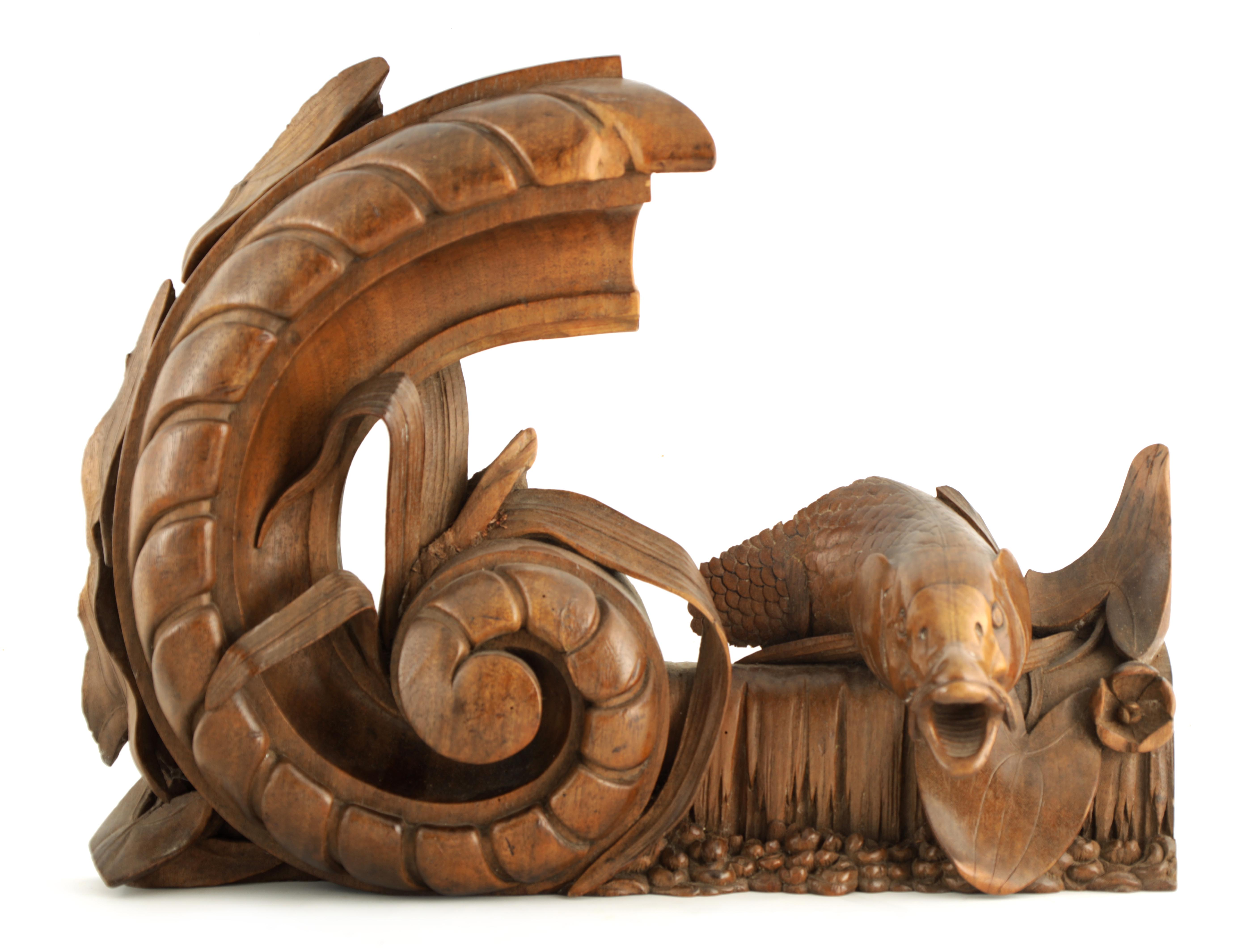 A 19TH CENTURY WALNUT CARVING OF A CARP next to a gadrooned scroll with reeds 49cm wide 38cm high