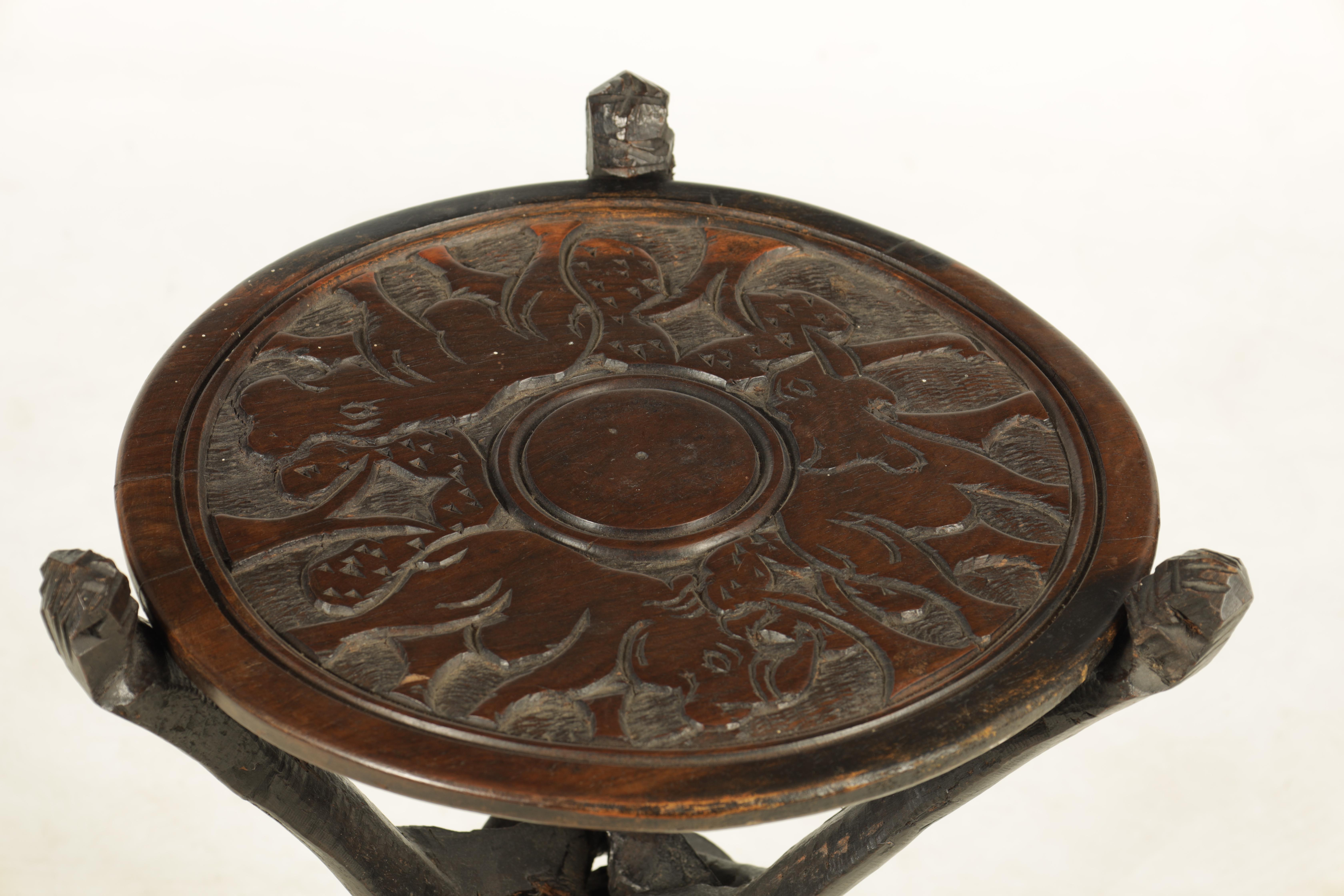 A LATE 19TH CENTURY AFRICAN HARDWOOD FOLDING TABLE the circular top relief carved with Rhinosorus - Image 2 of 7