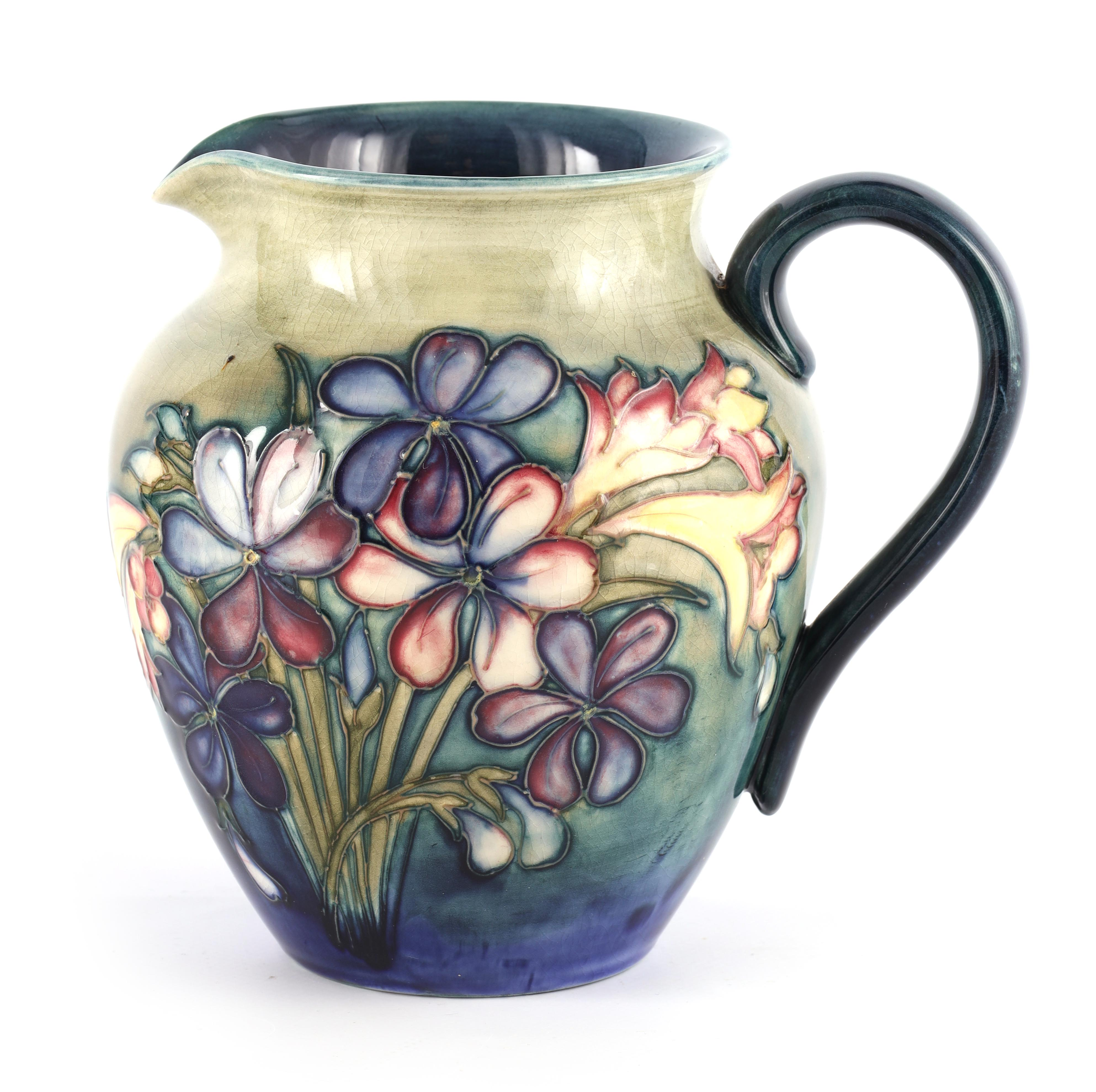 A MOORCROFT SHOULDERED TAPERING JUG tube lined and decorated in the spring flowers pattern on a