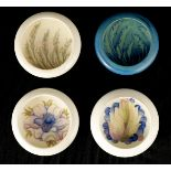 A COLLECTION OF FOUR MOORCROFT CIRCULAR SHALLOW DISHES WITH CURVED RIMS three cream ground with