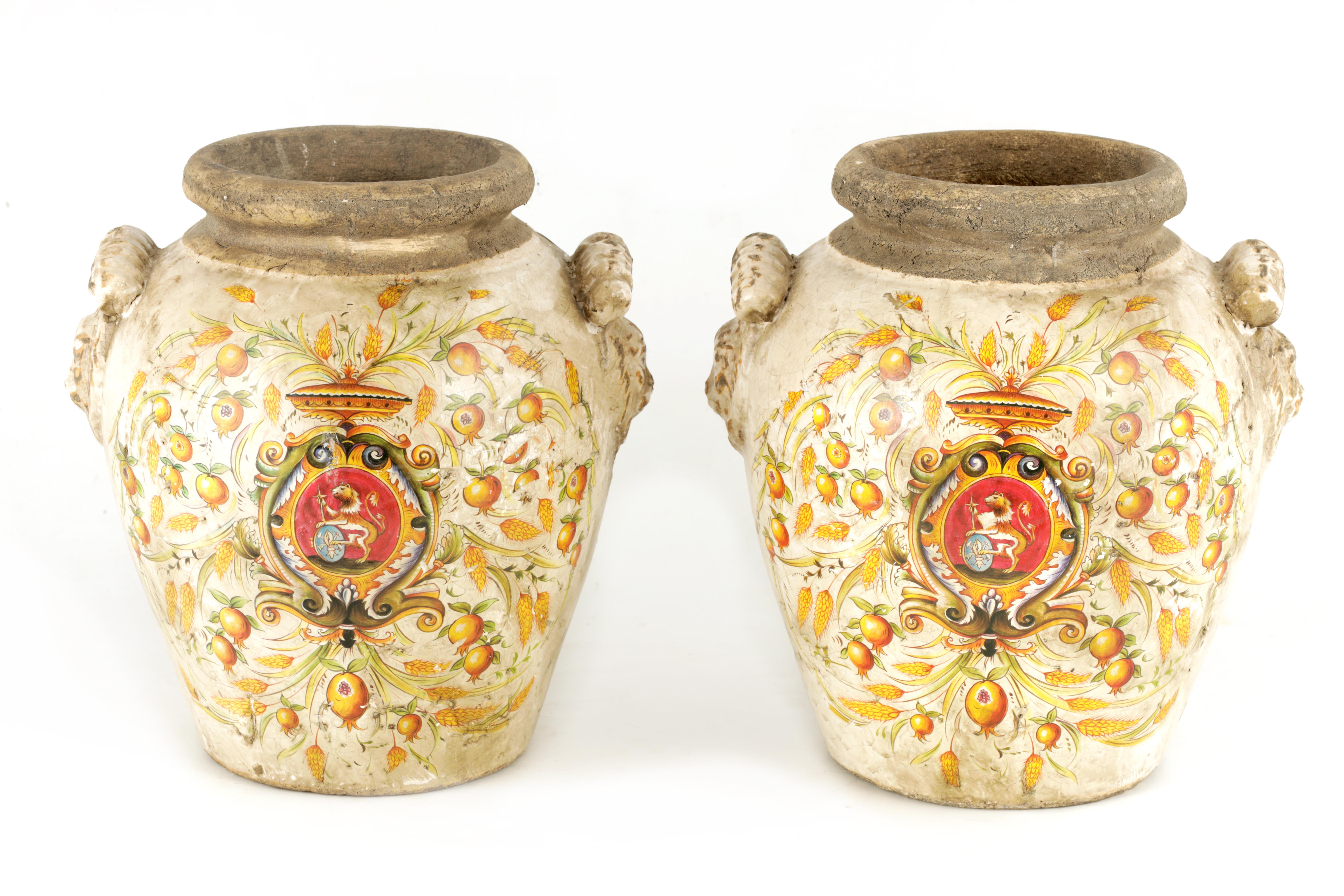 A PAIR OF EARLY ITALIAN EARTHENWARE ARMORIAL VASES with lion mask handles and painted armorials