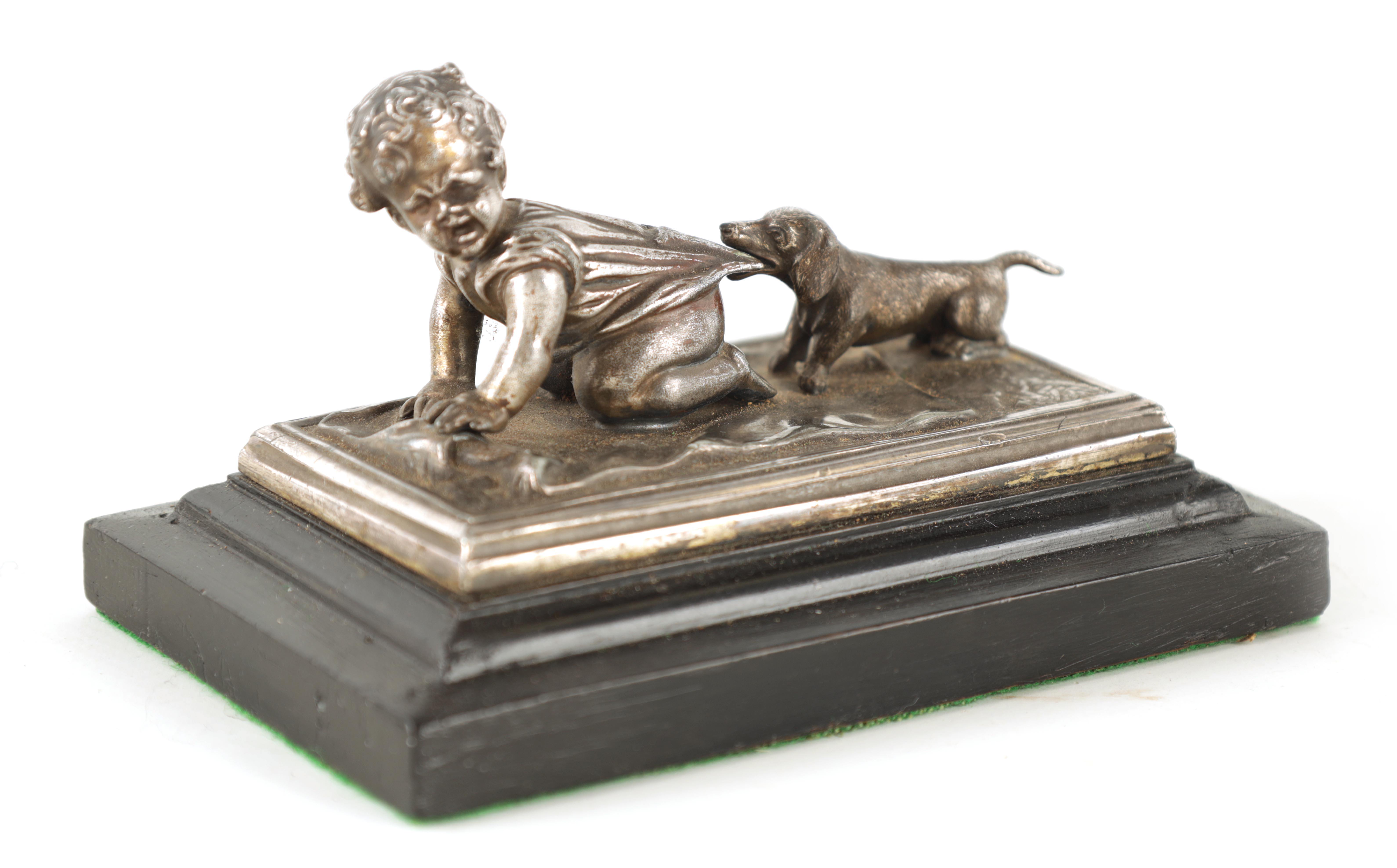 AN UNUSUAL 19TH CENTURY W.M.F. SILVERED METAL DESK PAPERWEIGHT depicting a small child with a