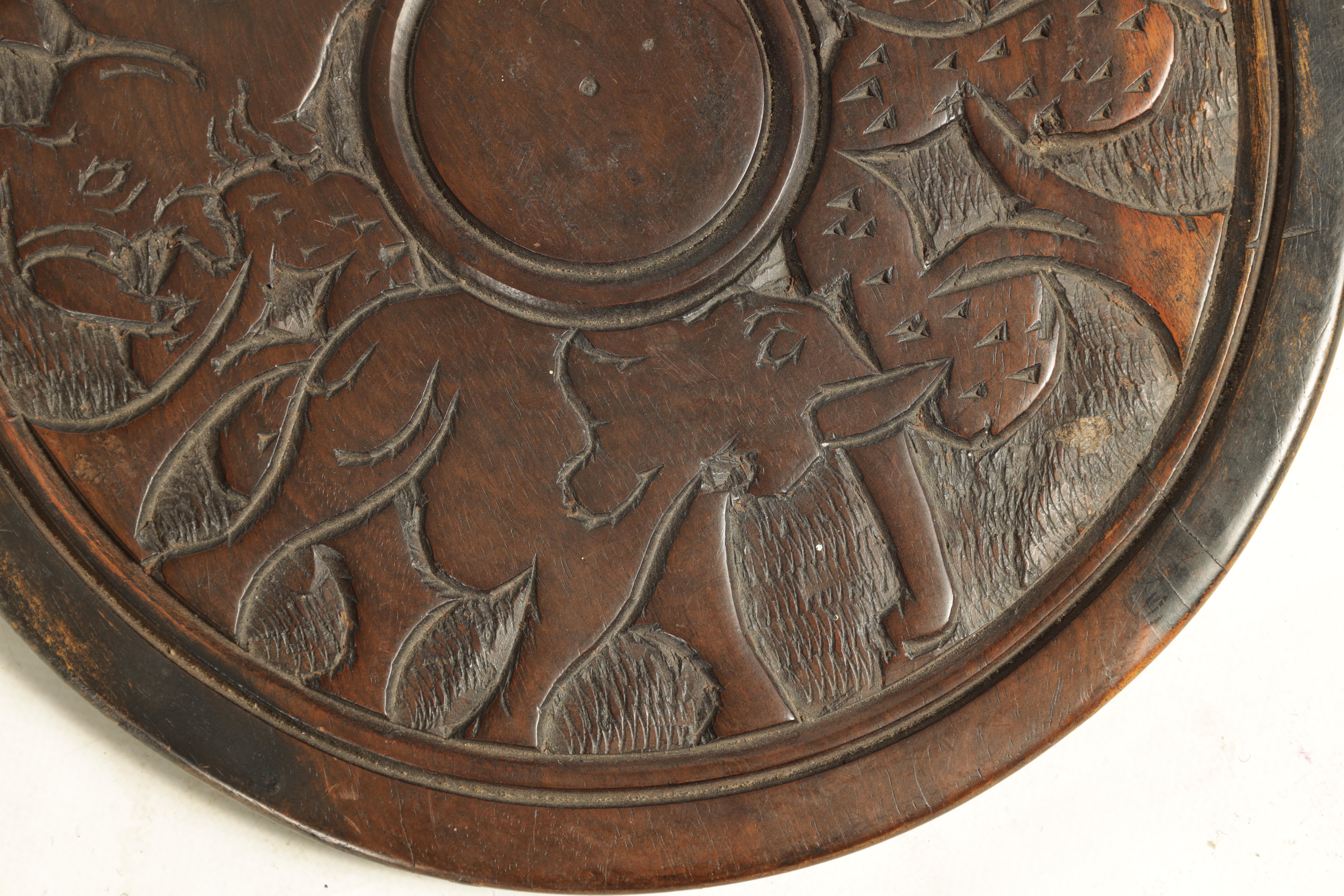 A LATE 19TH CENTURY AFRICAN HARDWOOD FOLDING TABLE the circular top relief carved with Rhinosorus - Image 7 of 7