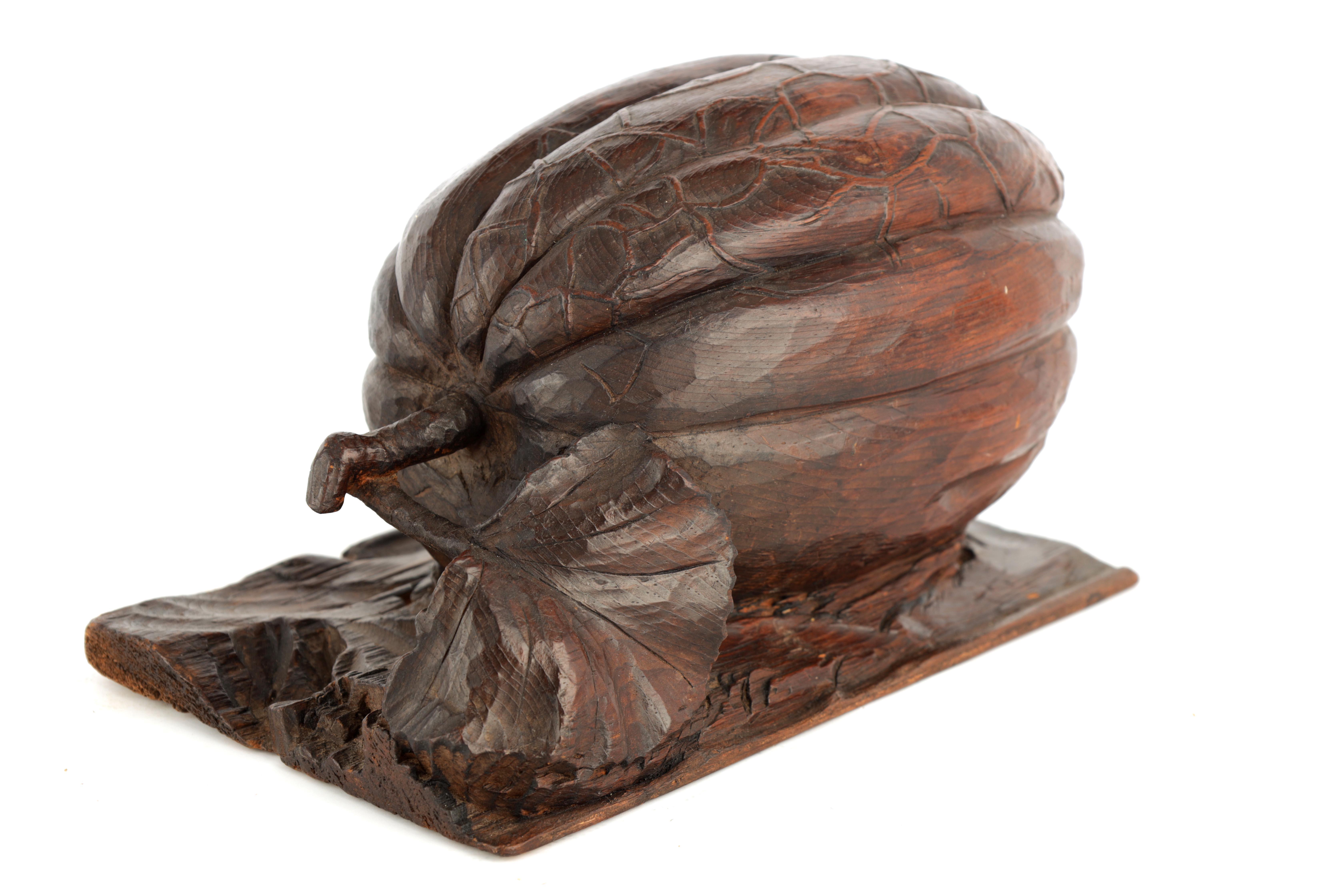 A 19TH CENTURY CARVED OAK SCULPTURE modelled as a pumpkin on a naturalistic base 23.5cm wide, 13cm
