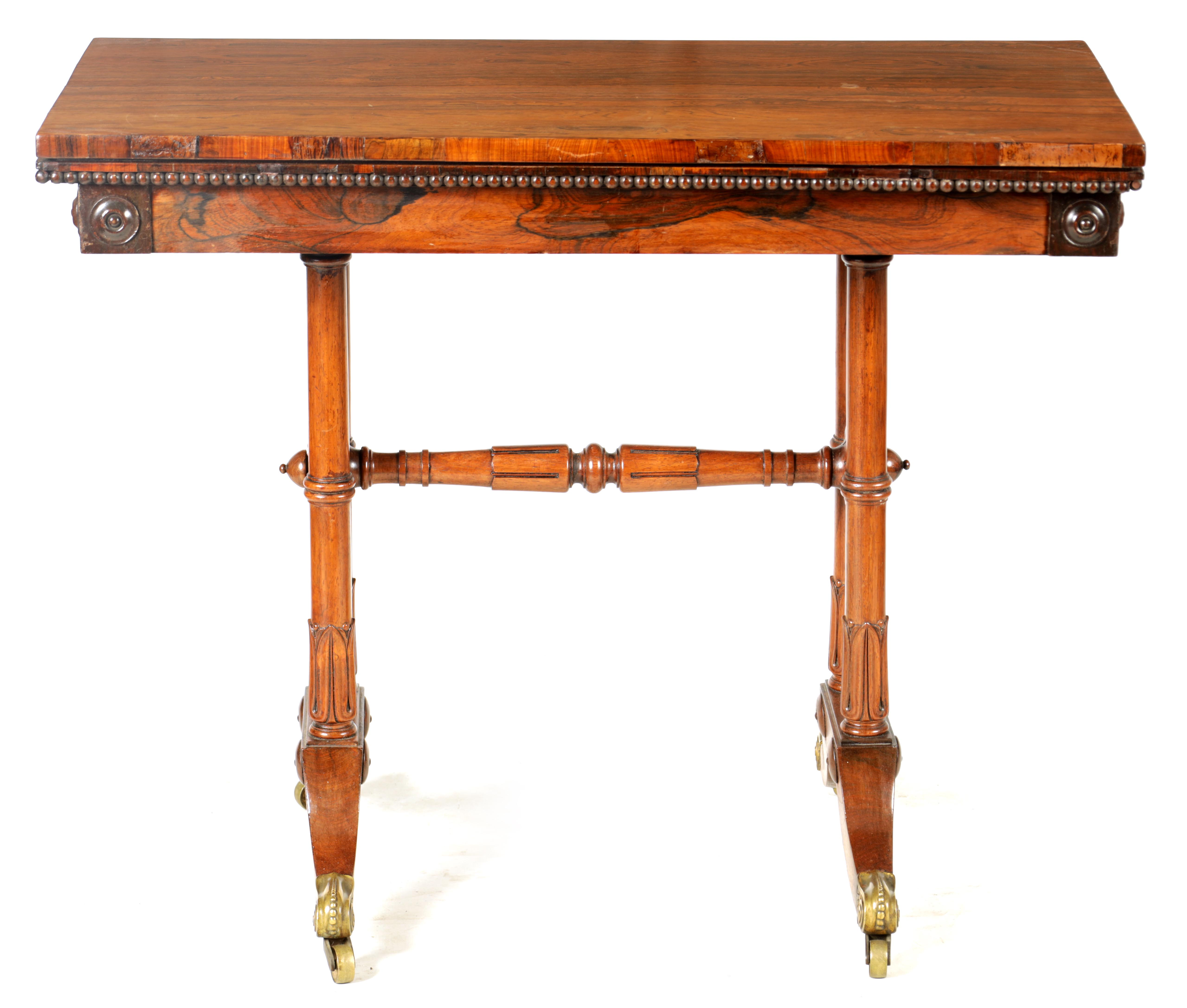 A REGENCY FIGURED ROSEWOOD CARD TABLE IN THE MANNER OF T & G SEDDON with revolving top revealing a