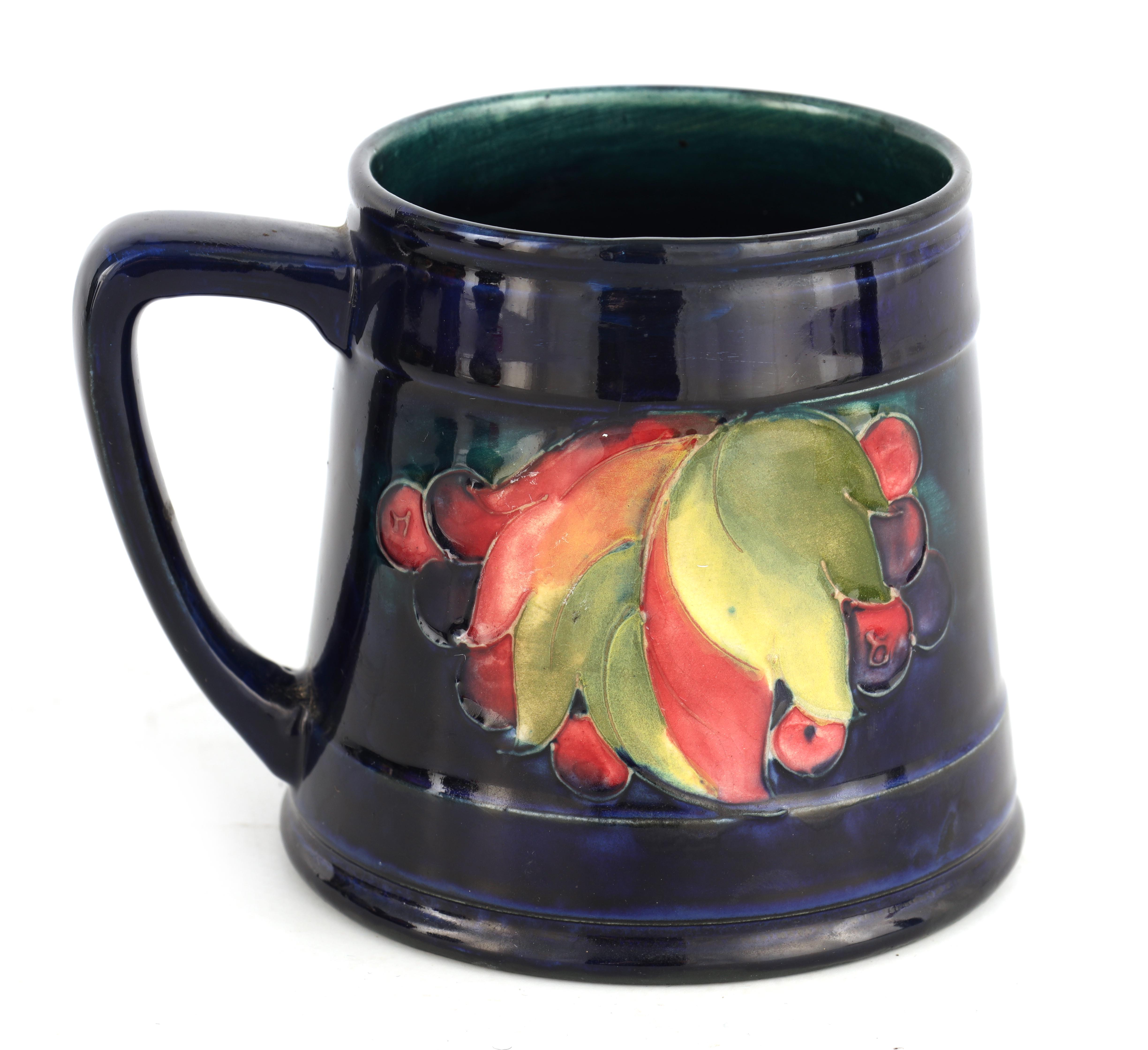 A 1930S/40S MOORCROFT TAPERING MUG tube lined and decorated with Leaf and Berry sprays, 10cm high,