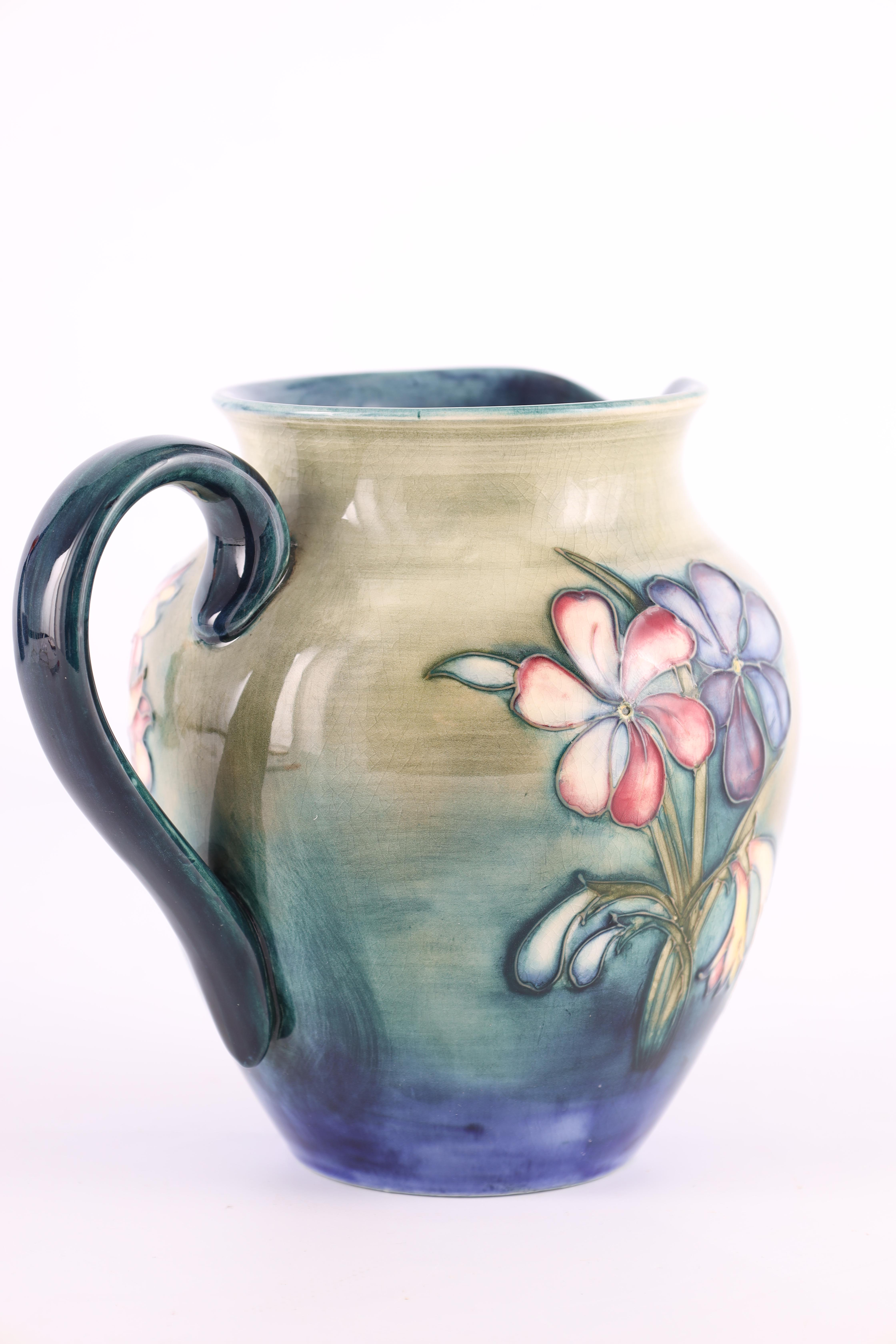 A MOORCROFT SHOULDERED TAPERING JUG tube lined and decorated in the spring flowers pattern on a - Image 5 of 6