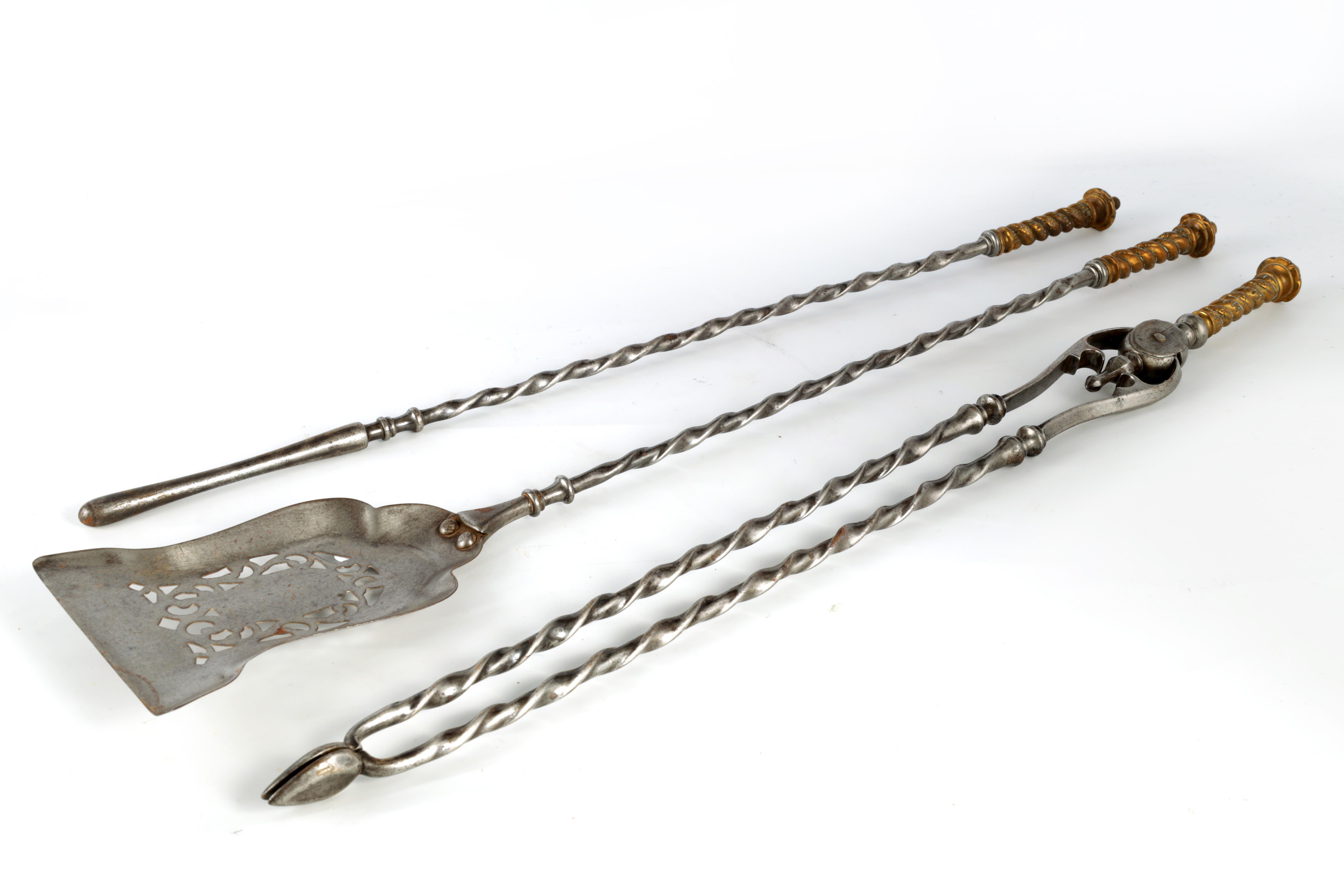 A SET OF REGENCY STEEL AND BRASS FIRE IRONS with cast brass handles and barley twist stems, the