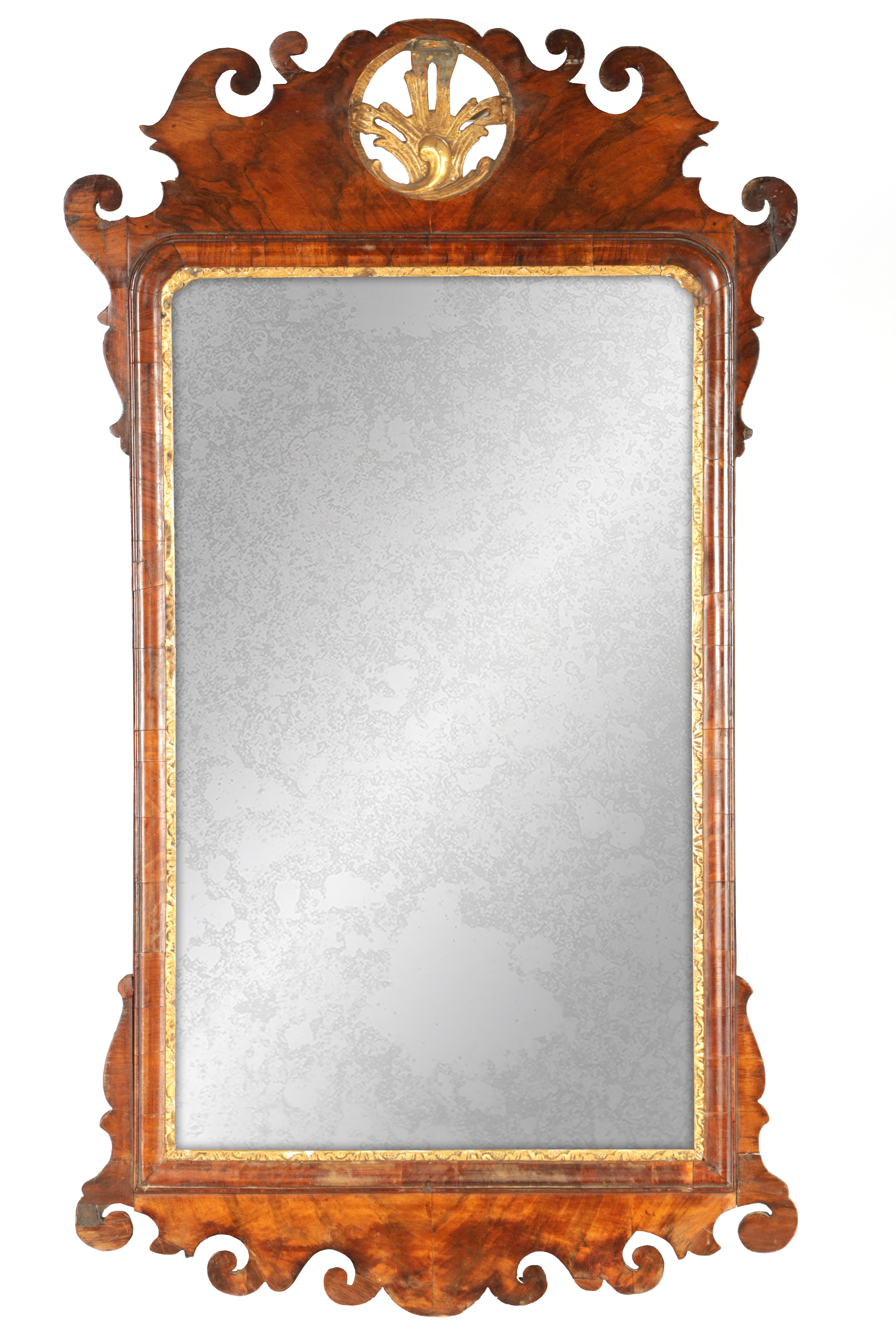 AN 18TH CENTURY WALNUT PIER MIRROR with shaped scrolled frame and gilt carved rococo pediment, the