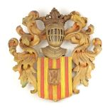 A LATE 19TH CENTURY CARVED AND PAINTED WOOD ARMORIAL PLAQUE surmounted by a knights helmet above a