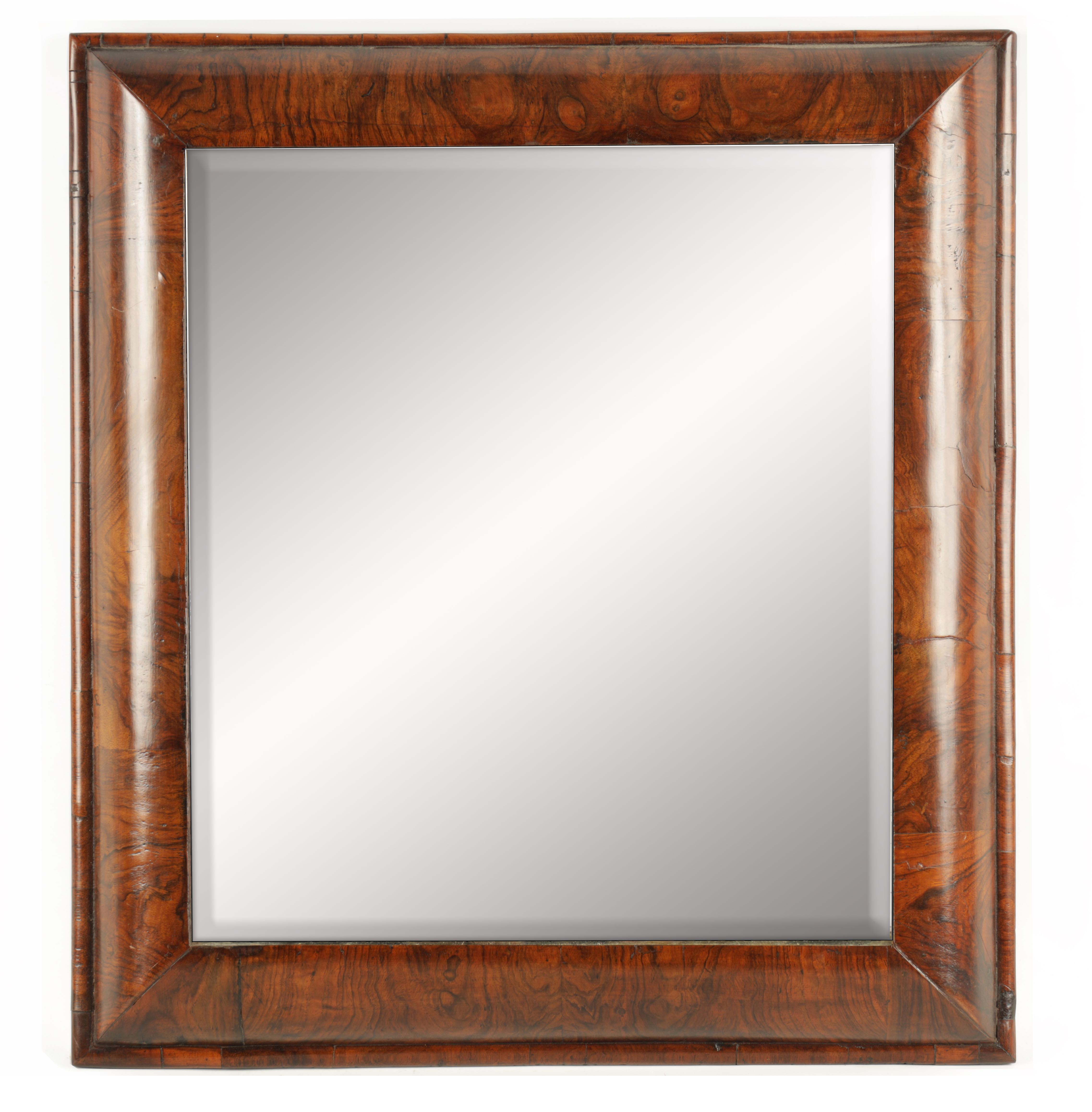 A WILLIAM AND MARY FIGURED WALNUT D SHAPED HANGING MIRROR fitted with original bevelled mirror