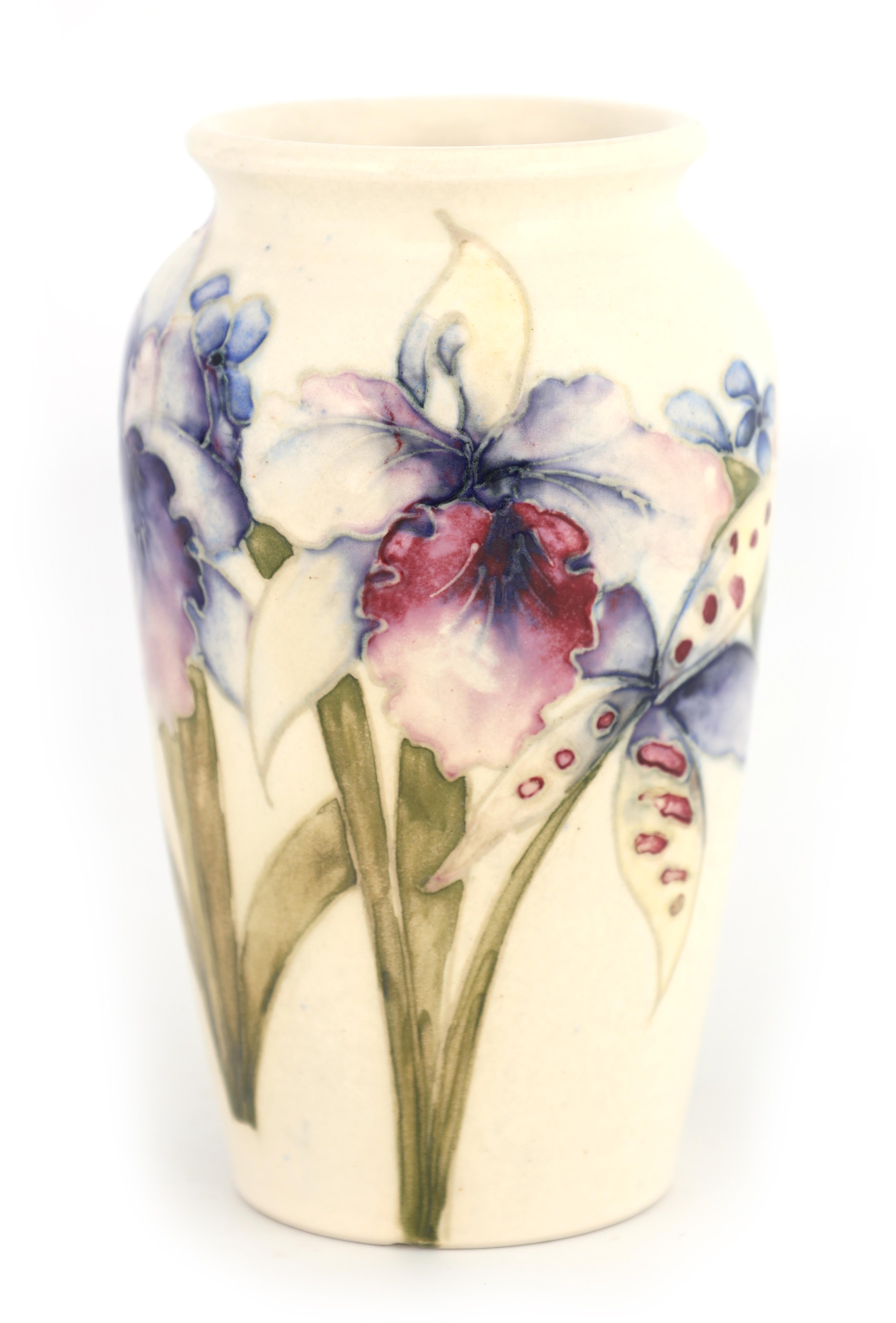 A MOORCROFT SMALL TAPERING SHOULDERED VASE decorated with orchid sprays on a cream ground, 13cm